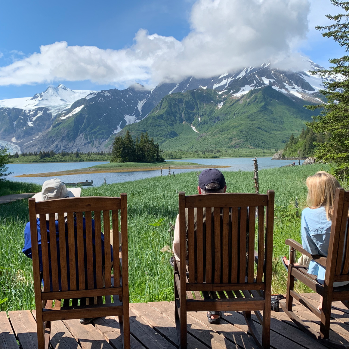 Back-view of travelers sitting in chairs enjoying view of Alaskan mountains.