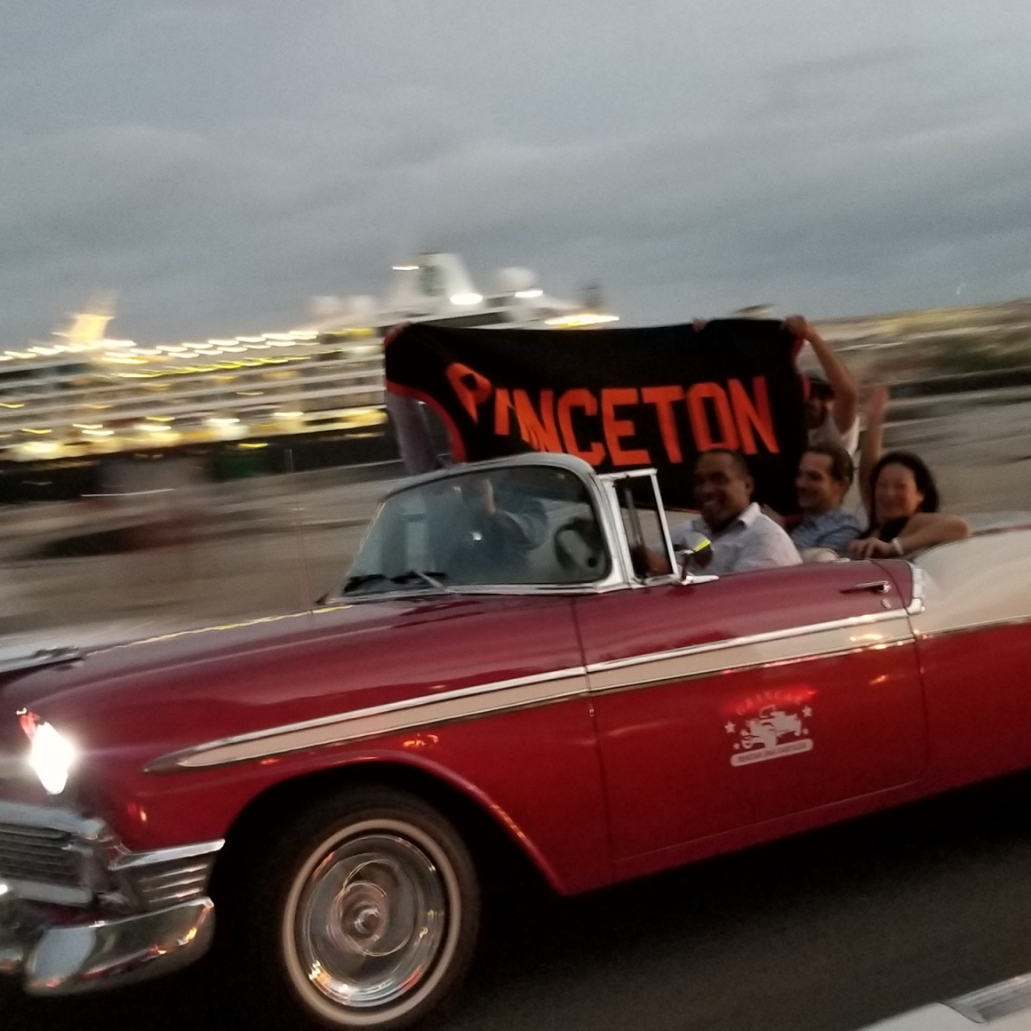 Travelers with Princeton banner driving red vintage car in Cuba