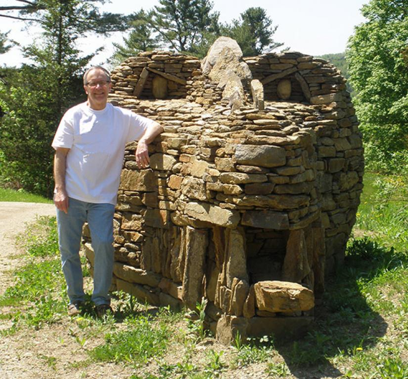 Ray Hartman '69 stands beside the stone dragon he designed.